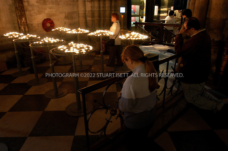 4/1/2005--Paris, France..Worshippers at Paris's Notre Dame Cathedral light candles and offer prayers as the Pope's condition in the Vatican continues to worsen...All photographs ©2005 Stuart Isett.All rights reserved.
