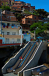 The barrio of Comuna 13 clings to the side of a steep hillside in Medellin were residents had to climb up and down many steps to get into town and back.  Now Medellin is the first city in the world to build a series of outdoor escalators as public transport, creating mobility solutions for the neighborhood with such difficult accessiblity.  The escalators are divided into six sections and have shortened the trip from a 35 minute hike by foot to six minutes.  In the photo a boy is seen riding the escalator down as he is watched by one of the construction personel.