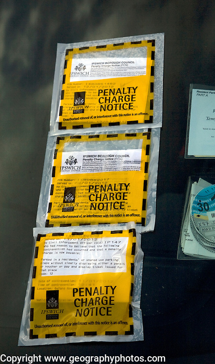 Three penalty charge parking notice tickets on car windscreen