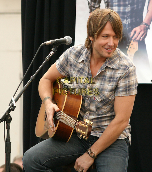 KEITH URBAN.is joined by Verizon Wireless and Samsung Mobile as he makes an in-store appearance for his fans at the Verizon Wireless store in Pasadena, California, USA, November 21st 2009                                                                   .half length music concert gig live on stage grey gray brown plaid checked check shirt microphone tattoo bracelets  guitar sitting jeans .CAP/RKE/DVS.©DVS/RockinExposures/Capital Pictures