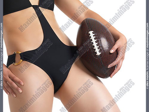 Sexy young woman in black trendy swimsuit with a football in her hand
