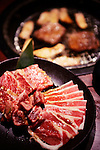 Plates with meat at Japanese grill restaurant. Yakiniku, Japanese barbecue.