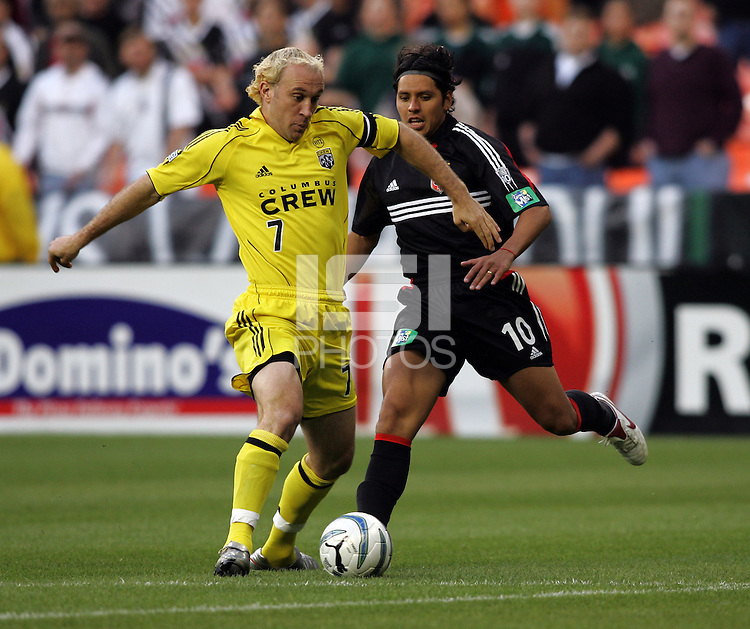 7 May 2005. Columbus' Simon Elliott (7) dribbles the ball away from DC United's Christian Gomez (10) at RFK Stadium in Washington, DC.