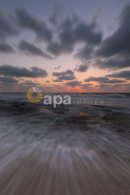 The picture taken on August 14, 2018 shows the sunset on the beach of Deir al-Balah in the center of Gaza Strip. Photo by Mahmoud Khattab