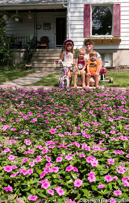 As a fifth anniversary gift Todd Oliver filled his Kathleen Avenue home boulevard with 5,000 pink periwinkle plants for his wife Margaret. It took three people hours to plant the flowers which matched the paint on the home. With Margaret are; Charley, 4, pink helmet, Wesley, 3, red, and Lucas, 2, orange while napping was one-year-old Bradley.
