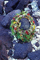 A lei offering placed on a rock