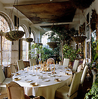 Oil paintings mounted on the ceiling hang above a large oval table laid for lunch in the orangery