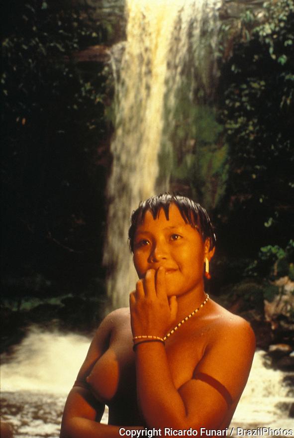 Portrait of young native Yanomami indigenous woman at waterfall, Amazon rain forest, Brazil.