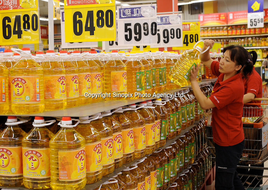 Staff puts cooking oil on shelf in Shenyang, China. The British retailer is undergoing an aggressive expansion and attempting to capture the growing middle class market in food and other domestic merchandise in China..