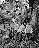 PERU, Amazon Rainforest, South America, Latin America, portrait of a family sitting together on bench (B&W)