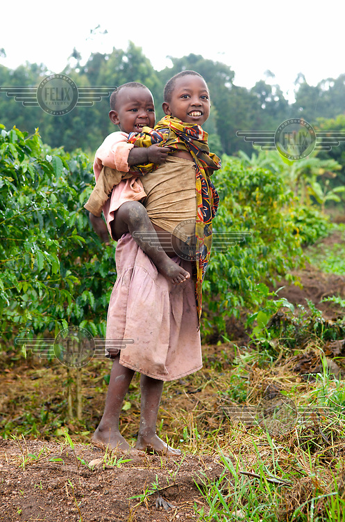 A young girl carries a baby on her back.