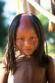 Bacaja village, Amazon, Brazil. Young boy with body and face paint, shaved head and botoque lip plate hole; Xicrin tribe.