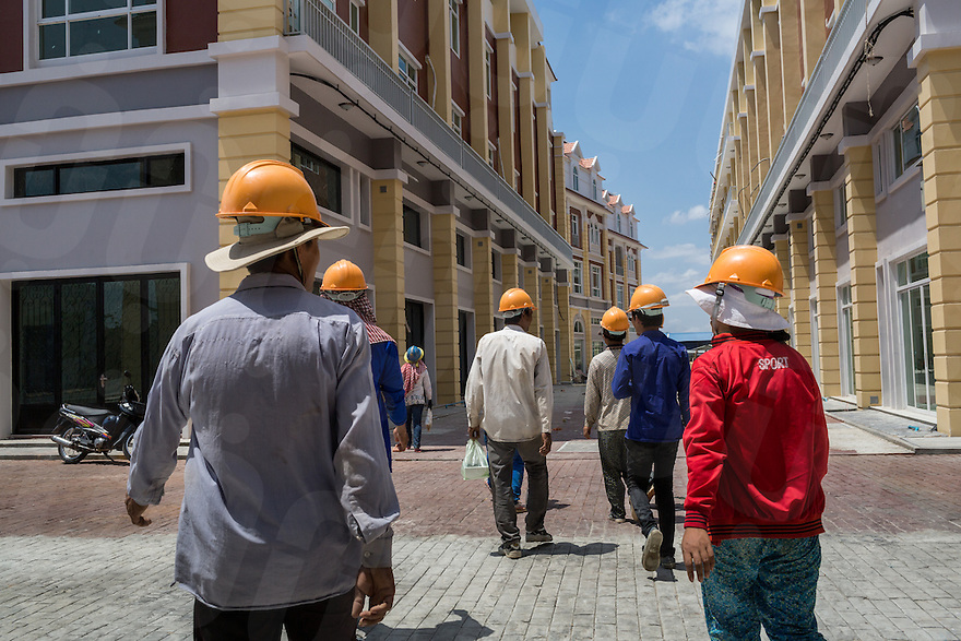 March 30, 2014 - Phnom Penh, Cambodia. Constuction workers walk through new buildings on Koh Pich island. The new development called La Seine is intended as a replica of the French Riviera . © Nicolas Axelrod / Ruom