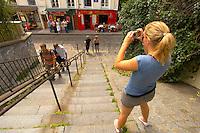 Young women taking a photo of cafes - Montmartre, Paris