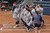 GREENSBORO, NC - MARCH 11: Kayleigh Willis #12 of UNC Greensboro is met by her teammates after hitting a three run home run during a game between Northern Illinois and UNC Greensboro at UNCG Softball Stadium on March 11, 2020 in Greensboro, North Carolina.