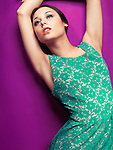 Fashion photo of a young beautiful woman in vintage style green dress on brigt purple background