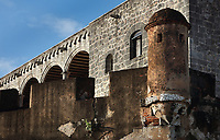 Crenelated wall with corner turret, and behind, the Alcazar de Colon, or Columbus Alcazar, built 1510-12 in Gothic Mudejar style, under Diego Colon, son of Christopher Columbus, who was 4th Governor of the Indies, in the Colonial Zone of Santo Domingo, capital of the Dominican Republic, in the Caribbean. The building houses the Museo Alcazar de Diego Colon, displaying Gothic and Renaissance European art. Santo Domingo's Colonial Zone is listed as a UNESCO World Heritage Site. Picture by Manuel Cohen