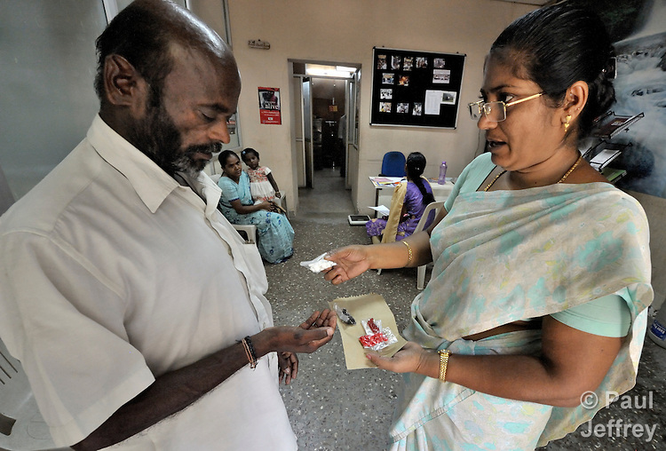 M. Palanivel gets medications from nurse R. Sugandhi at the Lutheran Church-sponsored Gurukul Clinic in Chennai, India. The patient is HIV positive and comes to the clinic because it offers specialized care for people living with HIV and AIDS.
