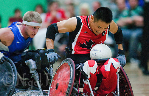 15 AUG 2011 - LEEDS, GBR - Canada's Ian Chan races to the goal line pursued by Great Britain's Aaron Phipps during the wheelchair rugby exhibition match between the two teams .(PHOTO (C) NIGEL FARROW)