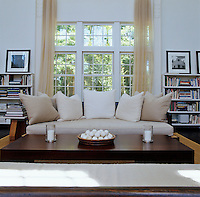 A deep sofa filled with large cushions in front of the large window in the living room is flanked by bookshelves