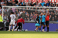 Pictured: Neil Taylor of Swansea is seen by team physios after suffering an injury from Peter Odemwingie of West Bromwich Albion (2nd R) who is shown a yellow card from match referee Martin Atkinson. Saturday 17 September 2011<br />