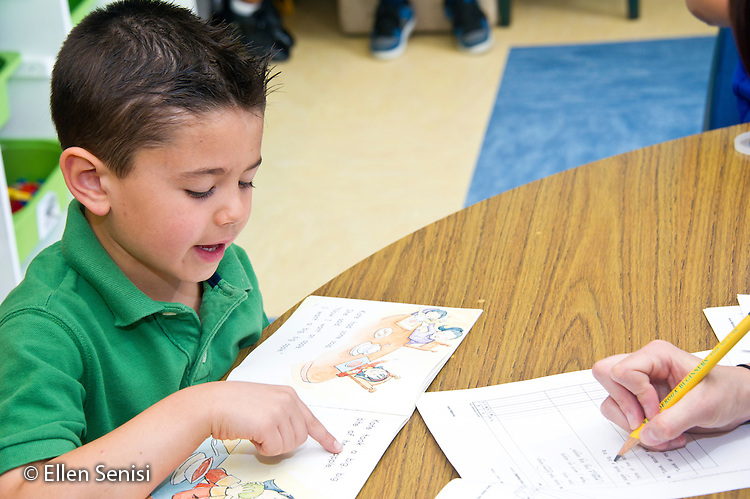 MR / Schenectady, NY. Zoller Elementary School. Kindergarten. Teacher assesses student's (boy, 5) reading ability in detail. She is recording the words he knows as well as the ones he misses. MR: Oco5, San10. ID: AL-gKs. © Ellen B. Senisi