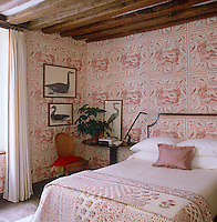The red and white Schumacher wallpaper in a guest bedroom features Swedish naturalist bird prints and the red and white theme is continued in the curtains and bedding