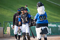 Missoula Osprey catcher Nick Dalesandro (8) walks past mascot Ollie Osprey before a Pioneer League game against the Grand Junction Rockies at Ogren Park Allegiance Field on August 21, 2018 in Missoula, Montana. The Missoula Osprey defeated the Grand Junction Rockies by a score of 2-1. (Zachary Lucy/Four Seam Images)