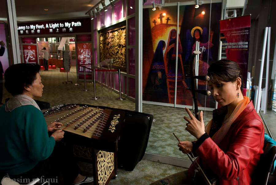An exhibition of Chinese christian artifacts (bibles, posters, icons etc.) at the Crystal Cathedral - Chinese musician practice before going onstage for an evening performance<br />
