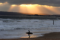 BNPS.co.uk (01202 558833)<br /> Pic: ZacharyCulpin/BNPS<br /> <br /> Pictured: A spectacular sunset breaks through the clouds.<br /> <br /> Strong coastal winds brought huge waves to Bournemouth beach last night. Surfers braved the cold weather and made most of the conditions at Bournemouth Pier.