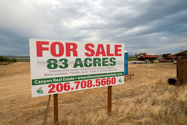 8/21/2012--Quincy, WA...83 acres for sale in Quincy, WASH. the sign reads that the lot is near both Yahoo and Microsoft. Behind sit combine harvesters used to harvest beans...Quincy has seen rapid growth of data centers, or server farms, spurred on by tax breaks and low cost electricity produced by the Grant Count PUD's nearby hydroelectric dams. Microsoft and five other companies, including Yahoo and Dell, have brought big, energy-hungry data centers to Quincy in recent years, converting former bean fields into vital hubs on the internet...©2012 Stuart Isett. All rights reserved.