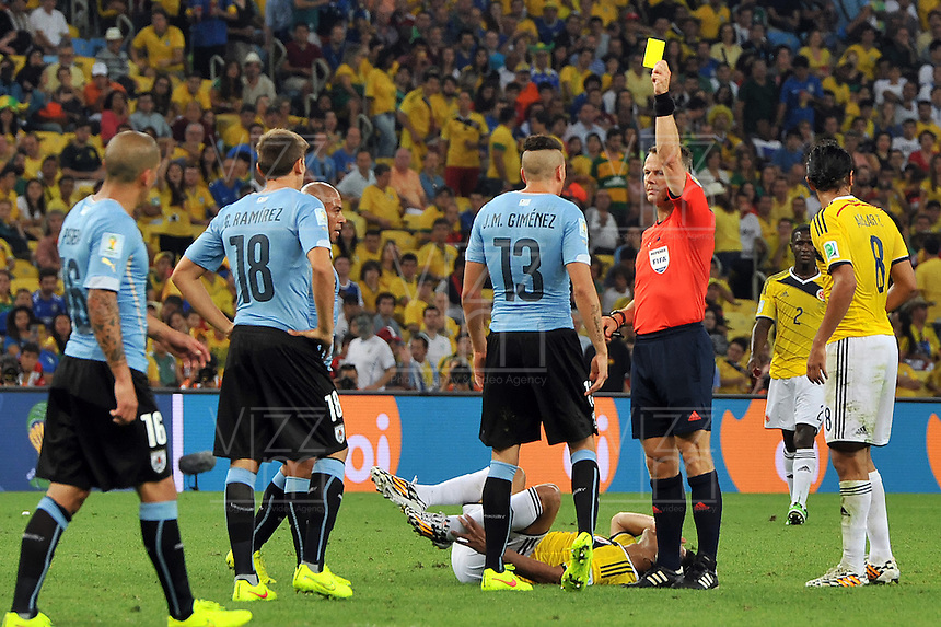 RIO DE JANEIRO - BRASIL -28-06-2014. Jose Gimenez (#13) jugador de Uruguay (URU) recibe la tarjeta amarilla del árbitro Bjorn Kuipers despues de haber cometido falta sobre Juan Cuadrado (#11) jugador de Colombia (COL)  durante partido de los octavos de final por la Copa Mundial de la FIFA Brasil 2014 jugado en el estadio Maracaná de Río de Janeiro./ Jose Gimenez (#13) player of Uruguay (URU) recives the yellow card from Bjorn Kuipers referee after committing a foul to Juan Cuadrado (#11) player of Colombia during the match of the Round of 16 for the 2014 FIFA World Cup Brazil played at Maracana stadium in Rio do Janeiro. Photo: VizzorImage / Alfredo Gutiérrez / Contribuidor