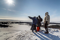 Tourists watch for Mitch Seavey from the hill at White Mountain over looking the Fish River at the White Mountain checkpoint on Tuesday March 16, 2015 during Iditarod 2015.  <br /> <br /> (C) Jeff Schultz/SchultzPhoto.com - ALL RIGHTS RESERVED<br />  DUPLICATION  PROHIBITED  WITHOUT  PERMISSION