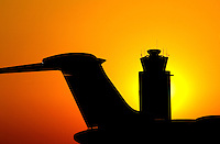 The tail of an airplane jet and the air traffic control tower are silhouetted against the setting sun at Charlotte-Douglas International Airport in Charlotte, North Carolina. Charlotte-based photographer has other images of transportation, airplanes on runways (and taking off and landing) and interior/exterior airport images of Charlotte-Douglas Intl Airport in portfolio.