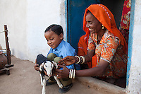 Suki's (not her real name) mother plays with Suki's young son in their house in Jhaju village, Bikaner, Rajasthan, India on 4th October 2012. Now 20, Suki was married off at age 12, but only went to live with her husband when she was 14. The three sisters, aged 10, 12, and 15 were married off on the same day by their maternal grandfather while their father was hospitalized. Her husband died three years after she moved in, leaving her with a daughter, now 6, and a son, now 4. She has no parents-in-laws and thus returned to her parents house after being widowed because her brother-in-law, who had become the head of the family after his brother's death, had refused to allow Suki to inherit her deceased husband's fair share of agriculture land. Although Suki's father wants her to remarry, she refuses to, hoping instead to be able to support her family through embroidery and tailoring work. The family also makes hand-loom cotton to subsidize their collective household income. Photo by Suzanne Lee for PLAN UK