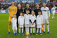 Dan Burn of Wigan Athletic (L), referee James Linington (C), Mike van der Hoorn of Swansea City (R) and children mascots during the Sky Bet Championship match between Swansea City and Wigan Athletic at the Liberty Stadium, Swansea, Wales, UK. Saturday 29 December 2018
