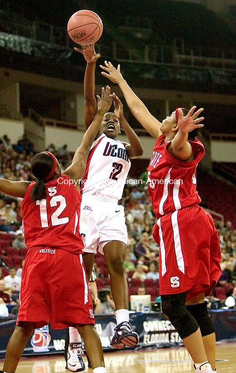 FRESNO, CA. 24 March 2007-032407SV13--#32 Kalana Greene of UConn takes a shot over #12 Marquetta Dickens and #55 Gillian Goring of NC State during the sweet sixteen round of the NCAA tournament at the Save Mart Center in Fresno, CA. Saturday.<br /> Steven Valenti Republican-American