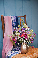 Detail of a vase of fresh flowers and two silk scarves on an old chair by the back door