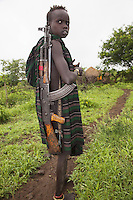 Ethiopia. Southern Nations, Nationalities, and Peoples' Region. Omo Valley. Mursi tribe. Agro-pastoralist group. Nomadic. A young boy, wearing a blanket tied over one shoulder, carries a Kalashnikov on his right shoulder. The AK-47 (also known as the Kalashnikov, AK, or Kalash) is a selective-fire (semi-automatic and automatic) assault rifle. The Mursi women are famed for wearing large plates in their lips (round clay plates placed into a cut in the lower lip) and ears. The disk is seen as a symbol of beauty and wealth.  The Omo Valley, situated in Africa's Great Rift Valley, is home to an estimated 200,000 indigenous peoples who have lived there for millennia. Amongst them are 8'000 Mursi who dwell between the Omo and Mago rivers. Southern Nations, Nationalities, and Peoples' Region (often abbreviated as SNNPR) is one of the nine ethnic divisions of Ethiopia. 11.11.15 © 2015 Didier Ruef
