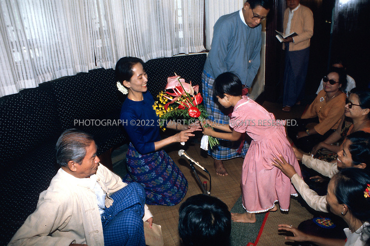 6/15/1995--Rangoon, Burma..Burmese opposition leader Aung San Suu Kyo accepts flowers from foloowers a week after her release from house arrest....All photographs ©2003 Stuart Isett.All rights reserved.This image may not be reproduced without expressed written permission from Stuart Isett.