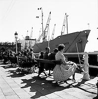 Mensen zitten aan de kade in de haven van Antwerpen in 1966.