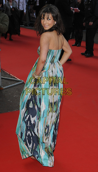 ROXANNE PALLETT.World Premiere of 'The Heavy' at the Odeon West End, Leicester Square, London, England, UK..April 15th 2010 .full length bracelets white strapless green print maxi dress hands on hips blue looking over shoulder .CAP/CAN.©Can Nguyen/Capital Pictures.