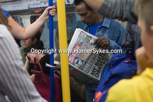 Man reading the Sun newspaper on London Underground Uk