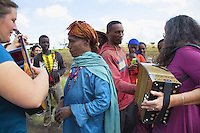 "Ethiopia. Southern Nations, Nationalities, and Peoples' Region. On the road to Sodo. Janik Michon (L) with the guitar and Chantal Marguerie (R) with accordion play music to a group of ethiopian farmers met along the road during a bus stop. Marc Vella is a french musician and a nomadic pianist. Over the last 25 years he has travelled with his Grand Piano in around forty countries to celebrate humanity. Creator of ""La Caravane amoureuse"" (The Caravan of Love) he takes people with him to say ""I love you"" to others and ""lovingly conquered"" their hearts and souls. The Omo Valley, situated in Africa's Great Rift Valley, is home to an estimated 200,000 indigenous peoples who have lived there for millennia. Southern Nations, Nationalities, and Peoples' Region (often abbreviated as SNNPR) is one of the nine ethnic divisions of Ethiopia. 5.11.15 © 2015 Didier Ruef"