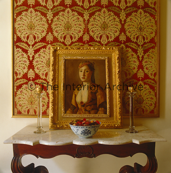 A gilt-framed portrait rests against a framed textile which hangs above the marble-topped console table