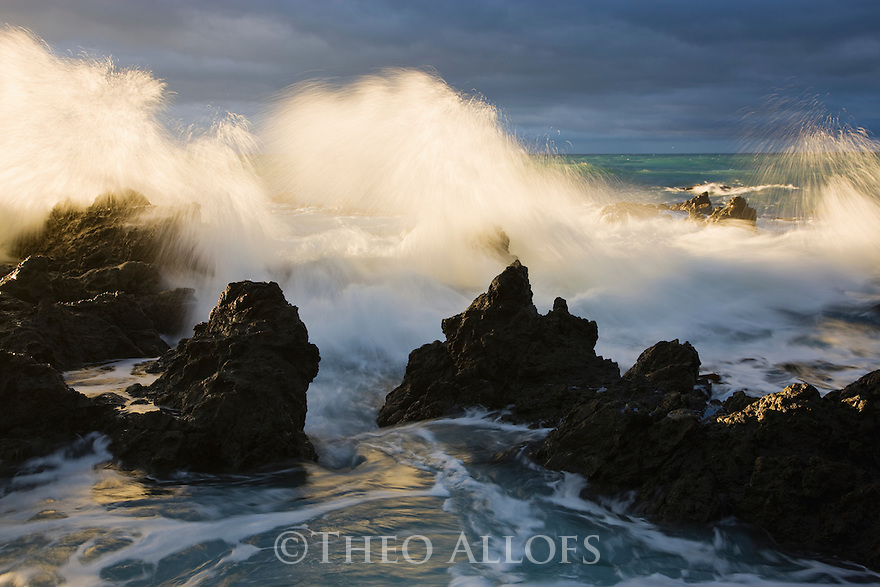 Rocky shore north of Kaikora at sunrise with dramatic storm clouds, South Island, New Zealand
