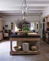 The stone-flagged kitchen is dominated by a bespoke kitchen island with a soapstone worktop