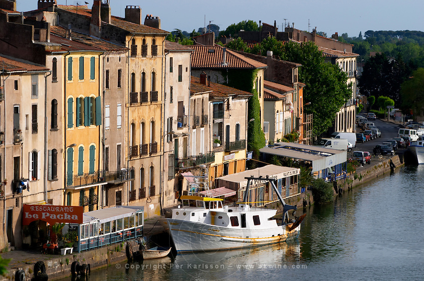 Restaurants along the l'Herault river. L'Herault river. A fishing boat. Agde town. Languedoc. France. Europe.