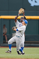 UCLA Bruin outfielder Brenton Allen (23) makes a catch while teammate Pat Valaika (10) avoids colliding with him during Game 4 of the 2013 Men's College World Series against the LSU Tigers on June 16, 2013 at TD Ameritrade Park in Omaha, Nebraska. UCLA defeated LSU 2-1. (Andrew Woolley/Four Seam Images)