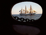 The U.S.S. Coast Guard Eagle training vessel is framed in the port hole of the historic Star of India Sailing Ship Museum, August 12, 1999 on the Pacific waters along the coast of San Diego during a joint sailing evolution performed by both ships. The Eagle a three-masted sailing Barque with 21,350 square feet of sail is home to Coast Guard Academy Cadets for a week the summer prior to attending the Academy. (AP Photo/ Victoria Arocho)